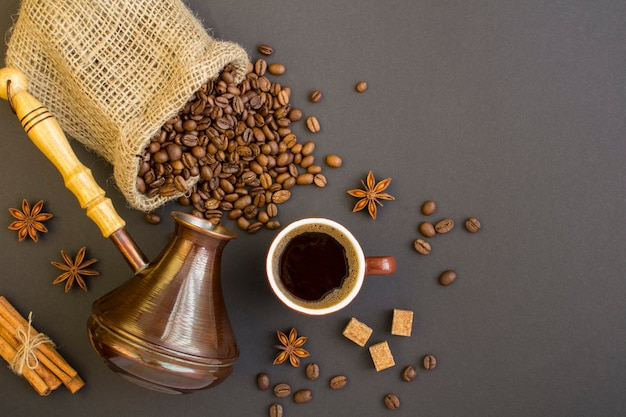 Draufsicht des schwarzen kaffees in der braunen tasse, in den kaffeebohnen und in der türke, um kaffee auf dem dunklen hintergrund zu machen