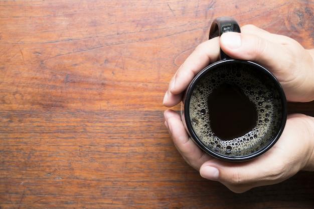 Draufsicht des schwarzen kaffees in einer schwarzen schale an hand auf holztisch mit kopienraum für text des bildes.