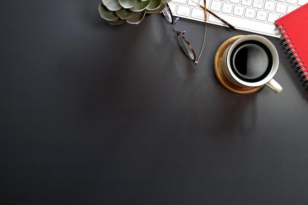 Draufsicht des schwarzen schreibtischs mit tastaturcomputer, büroartikel und kopienraum