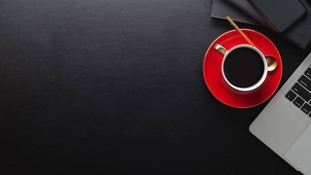 Draufsicht des schwarzen tisches mit kopierraum, kaffeetasse, laptop und notizbücher