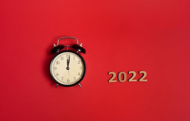 Draufsicht des schwarzen weckers mit mitternacht auf dem zifferblatt und holzzahlen, die das jahr 2022 symbolisieren. weihnachts- und neujahrsfeierkonzept über rotem hintergrund mit kopienraum für anzeige