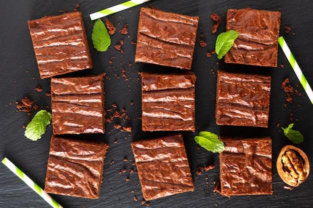 Draufsicht des selbst gemachten bäckereikonzeptes des lebensmittels von organischen schokoladenkuchen auf schwarzem schieferbrett