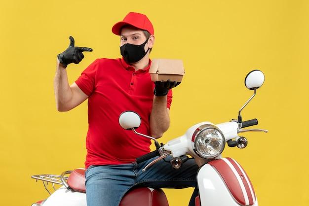 Draufsicht des selbstbewussten lieferers, der rote bluse und huthandschuhe in der medizinischen maske trägt, die auf roller sitzt, der ordnung zeigt
