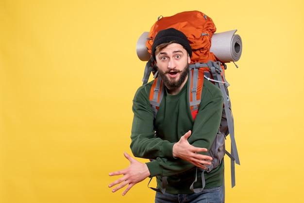 Draufsicht des selbstbewussten reisenden kerls mit packpack