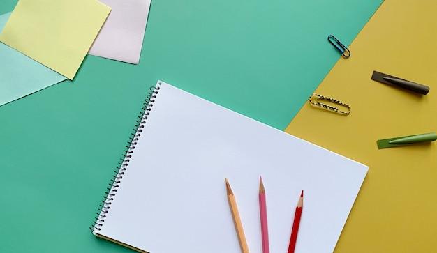 Draufsicht des skizzenbuchs mit buntstiften, büroklammern und bleistiftkappen auf grün und gelb