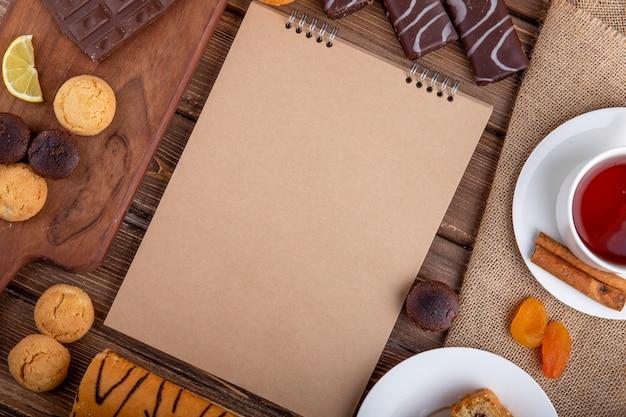 Draufsicht des skizzenbuchs verschiedener süßer gebäckkekse und einer tasse tee mit zimtstangen auf hölzernem hintergrund