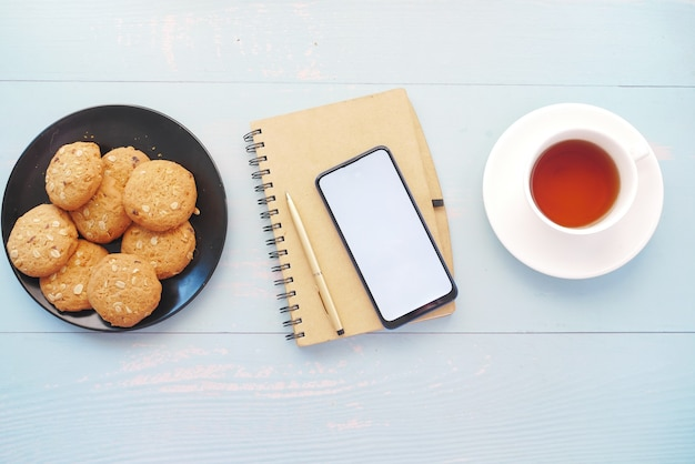 Draufsicht des smartphone-notizblock-tees und der kekse auf tisch