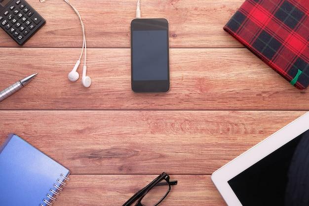 Draufsicht des smartphones, des digitalen tablets und des notizblocks auf tisch