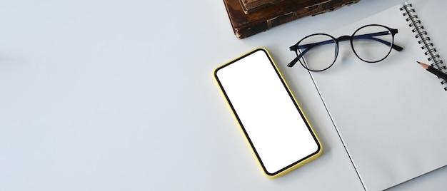 Draufsicht des smartphones mit leerem bildschirm, brille und notizbuch auf weißem schreibtisch