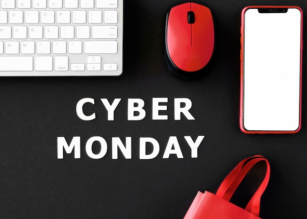 Draufsicht des smartphones mit tastatur und einkaufstasche für cyber-montag