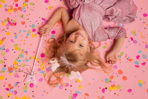 Draufsicht des smiley-mädchens im märchenkostüm mit konfetti