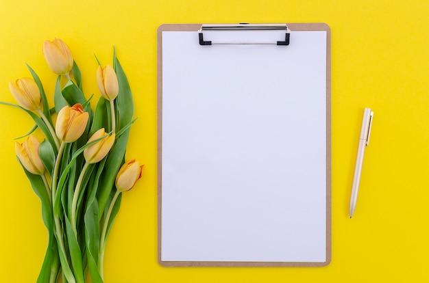 Draufsicht des sommerhintergrundes von gelben tulpen auf weißer tabelle mit klemmbrett und stift, kopienraum