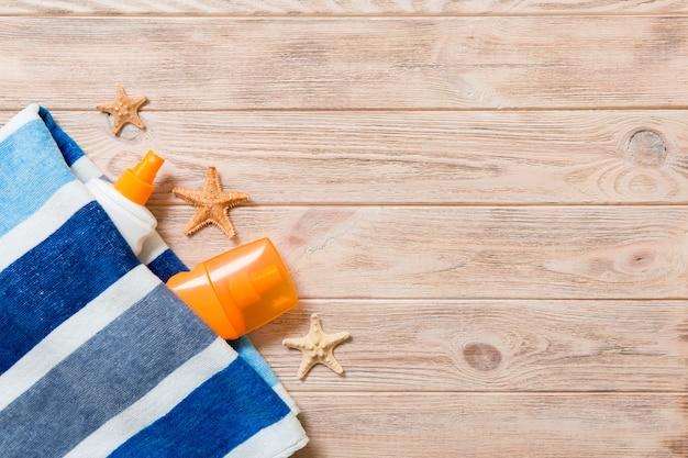 Draufsicht des sommerstrandpersonals mit kopienraum. muscheln oder seastar, eine flasche sonnencreme und ein blaues handtuch auf holzhintergrund. sommerferienkonzept