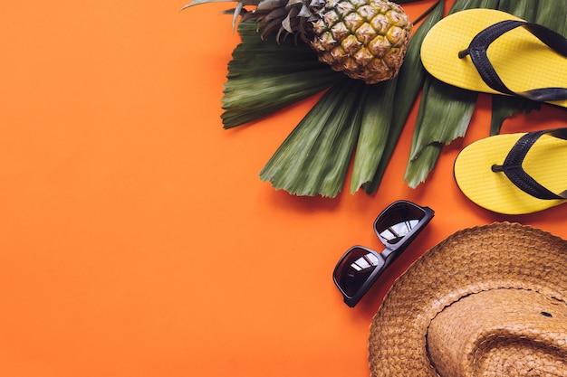 Draufsicht des sommerzubehörs auf orange hintergrund. kopieren sie platz