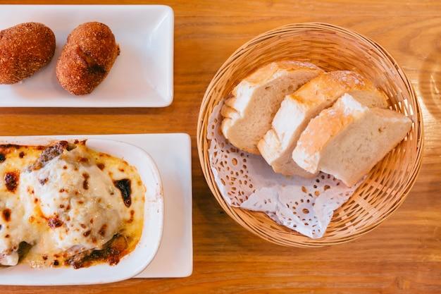 Draufsicht des spanischen frischen gebackenen brotes im korb mit lasagne und papas rellenas. diente als vorspeise.
