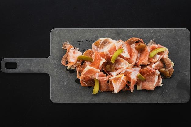Draufsicht des spanischen schinkens pata negra mit eingelegten gurken, die auf dem brett serviert werden
