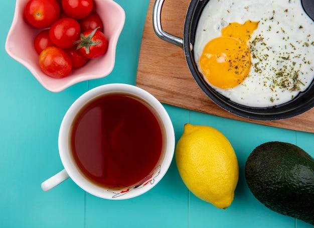 Draufsicht des spiegeleis auf pfanne auf holzküchenbrett mit tomaten auf weißer schüssel und zitrone auf blau