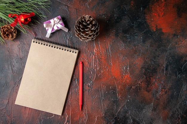 Draufsicht des spiralnotizbuchstifts nadelbaumkegelgeschenk und -geschenk auf dunklem hintergrund