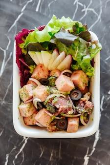 Draufsicht des stark geschnittenen würzigen salats des schinkens mit schwarzen oliven auf schwarzer marmortabelle im hintergrund.
