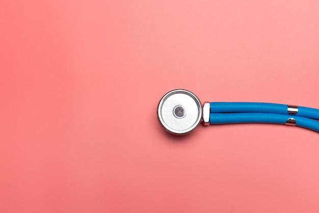 Draufsicht des stethoskops auf rosa hintergrund. flach legen und kopieren sie platz. medizinisches konzept.