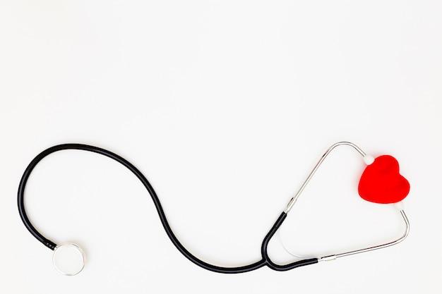 Draufsicht des stethoskops und des roten herzens auf weißem hintergrund