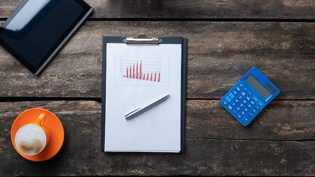 Draufsicht des stiftes, der auf einem papierkram mit grafiken und diagrammen auf einem schreibtisch neben digitalem tablett, taschenrechner und tasse frischem kaffee liegt.