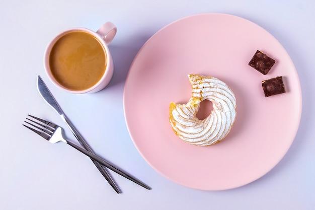 Draufsicht des stilllebens eines gebissenen kuchens auf einem rosa teller, besteck und einer tasse kakao oder kaffee mit milch. selektiver fokus, horizontale ausrichtung.
