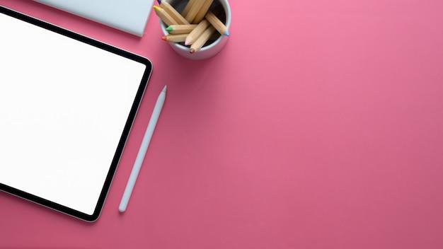 Draufsicht des stilvollen arbeitsbereichs mit digitalem tablett und kopierraum auf rosa tisch