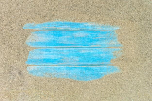 Draufsicht des strandsandes mit blauem hölzernem hintergrund.
