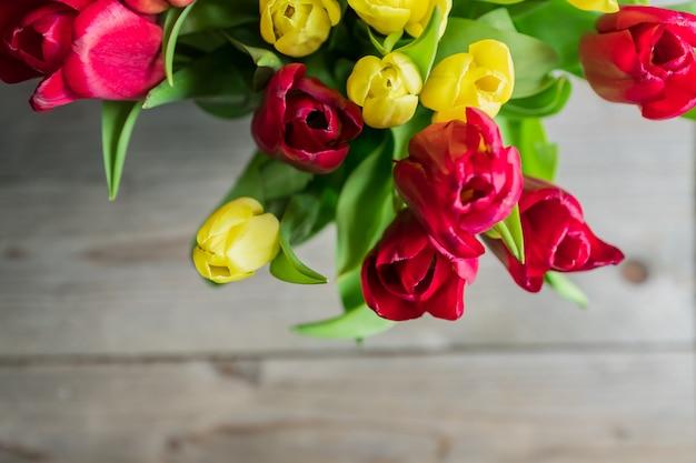 Draufsicht des straußes der roten und gelben tulpen. festliche grußkarte für muttertag oder geburtstag.