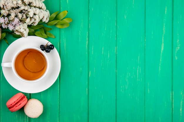 Draufsicht des straußes der weißen blumen mit einer tasse tee mit macarons auf einer grünen oberfläche