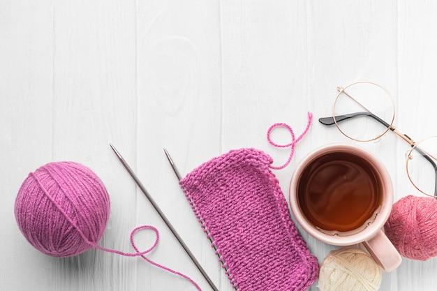 Draufsicht des stricksatzes mit garn und tee