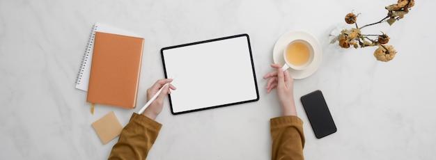 Draufsicht des studenten, der hausaufgaben mit mock-up-tablette auf marmortisch macht