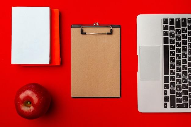 Draufsicht des studentenarbeitsraums mit offenem laptop und rotem apfel, andere lieferungen