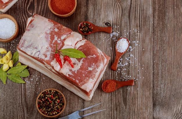Draufsicht des stückes des rohen schweinebauches mit salz und rotem paprika auf rustikalem holztisch