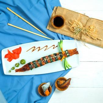 Draufsicht des sushi-drachen der traditionellen japanischen küche mit aalgurke und avocado auf blau und weiß