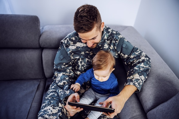 Draufsicht des tapferen soldaten, der die verlorene zeit mit seinem sohn wieder gut macht. mann, der kleinkind im schoß, tablette in den händen hält und cartoons beobachtet.