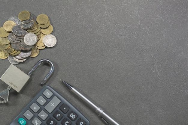 Draufsicht des taschenrechners, des verschlusses, des schlüssels, des stiftes und der münzen für finanz- und einsparung
