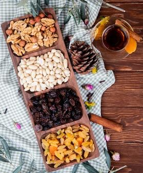 Draufsicht des tees im armudu-glas mit gemischten nüssen und getrockneten früchten in einer holzkiste auf holz