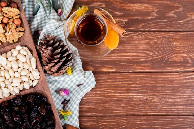 Draufsicht des tees im armudu-glas mit verschiedenen getrockneten nüssen und früchten auf holz mit kopienraum