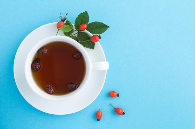 Draufsicht des tees mit dogrose auf der blauen oberfläche