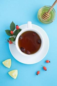 Draufsicht des tees mit dogrose und honig auf der blauen oberfläche