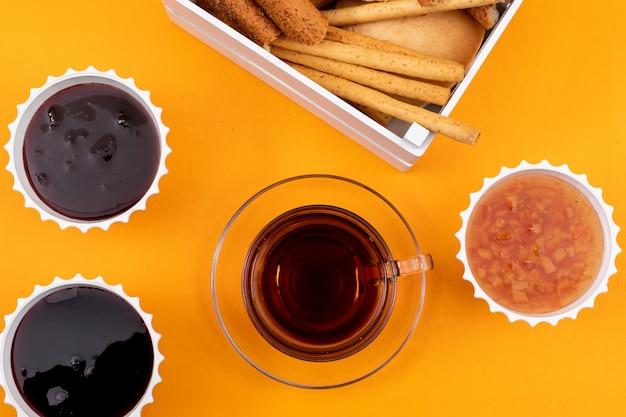 Draufsicht des tees mit marmelade und crackern auf gelber oberfläche horizontal