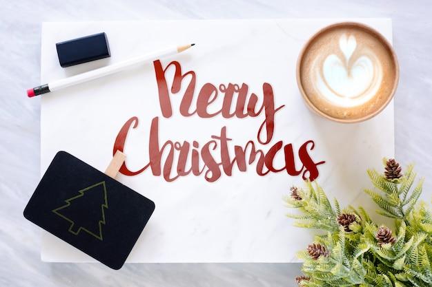 Draufsicht des textes der frohen weihnachten auf marmor mit tafel, bleistift, radiergummi-kiefernblatt und c
