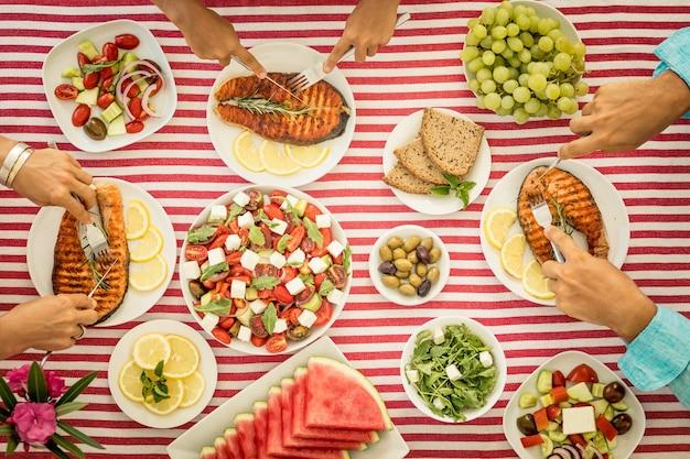 Draufsicht des tisches mit fisch, salaten, obst und gemüse