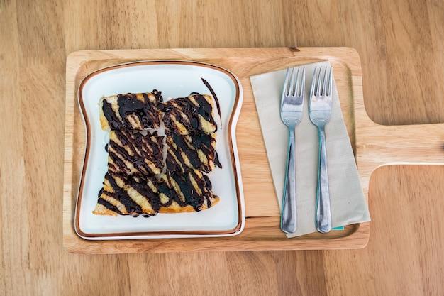 Draufsicht des toasts mit schokolade auf weißer platte und hölzerner behälter- und silbergabel.