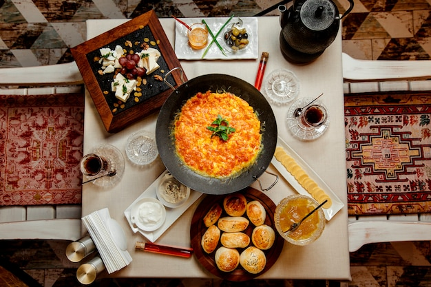 Draufsicht des traditionellen aserbaidschanischen frühstücks mit ei- und tomatenteller