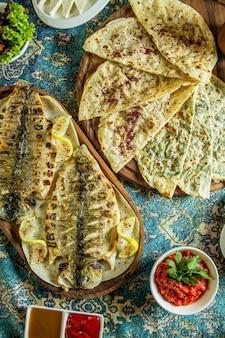 Draufsicht des traditionellen aserbaidschanischen gutabs mit fleischkräutern und kürbis serviert mit sumakh und gegrilltem fisch auf einem bunten teppich