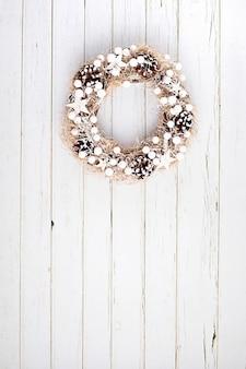 Draufsicht des traditionellen weihnachtskranzes mit kopienraum über neutralem hölzernem hintergrund. winterferien und weihnachtsfeier konzept