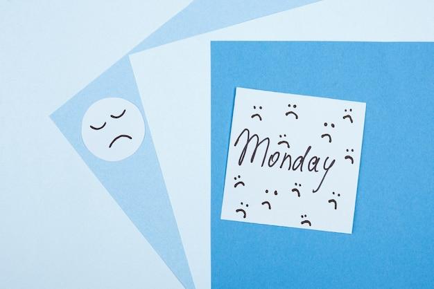Draufsicht des traurigen gesichts mit haftnotiz für blauen montag
